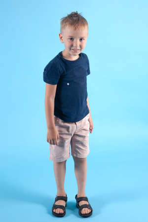 Little caucasian boy with blond hair stands on blue background. Suntan on hands and face, traces of mosquito bites on legs, summer casual wear. Positive emotions of real baby of active lifestyle.