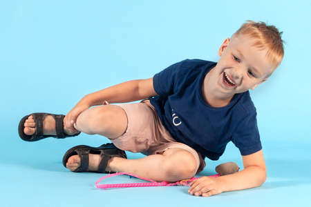 Pretty little caucasian boy falling down on blue background, cheerfully laughing. Blond hair, casual summer wear, pink toy. Innocence of childhood concept. Copy space.