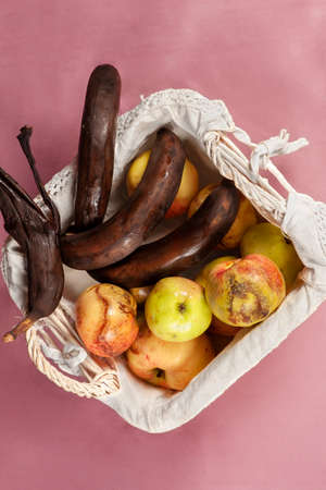 Top view on some overripe fruits in white wicker basket with dirty napkin, tainted bananas, half-peeled and rotten, apples with decay spots on purple background. Stale fruit concept. Indoors, copy space.