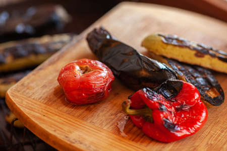 Vegetables baked on the grill lie on a wooden background. Tomato, eggplant, bell pepper and vegetable marrow with soot spots. Healthy food concept. Copy space.