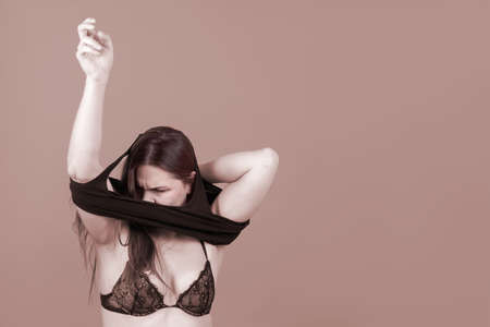Young caucasian woman puts on the black shirt. Half naked body is in the underwear, displeased face expression. Monochromatic picture, copy space.