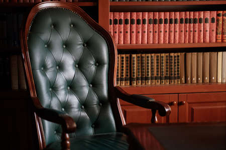 Dark solid interior of old library with books on the wooden shelves. Vintage classic chair green leather and red wood, antique table, luxury design with expensive natural details. Low exposure.