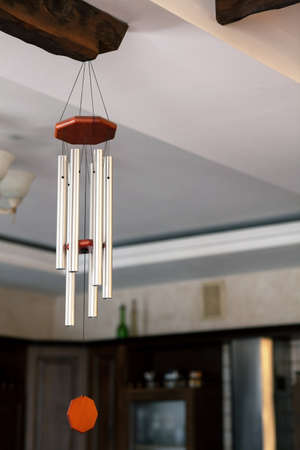 Traditional Chinese Feng shui interior object called chime tree or wind music, made from steel tubes. Relaxation, cleansing aura and defense from negative energy, hanging on the wooden bar on ceiling.