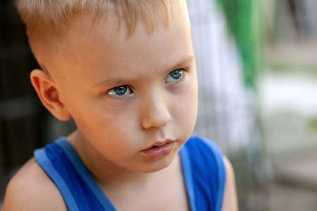 Close up portrait of beautiful baby boy with very serious look. Blond hair, blue eyes, strong emotions, sad face expression. Outdoors, copy space.