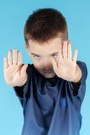 Close up portrait of pretty little Caucasian boy with blue eyes making stop gesture with both hands, seriously looking right to the camera. Cyan background. Concept of ban of children abuse.