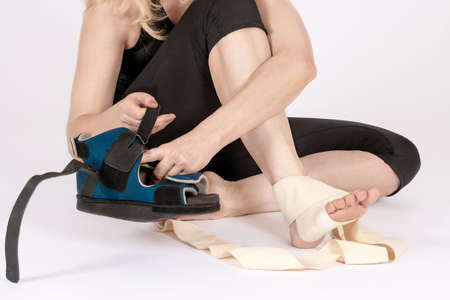 Female wearing sport clothes, sitting on the floor, bandages her leg and takes up the orthopedic boot. Recovery after trauma or surgery. White background, copy space.