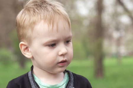 Close up portrait of cute Ð¡aucasian baby boy on green park background. Blue eyes, blond hair, looking to right side of shot. Spring time, outdoors, copy space.
