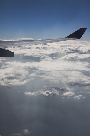 through window: Clouds and sky as seen through window of an aircraft.