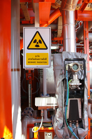 radioisotope: Flow meter, with high radiation sign.