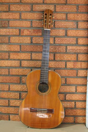 Spanish guitar propped in front of a brick wall as background