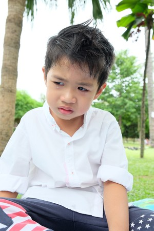 Boy crying while sitting in park