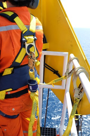 belaying: construction site worker at offshore with safety harness.