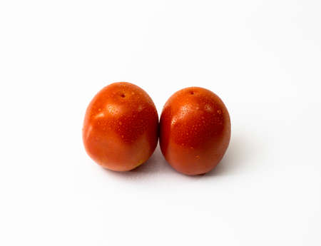 Two tomatoes on white background with water drops