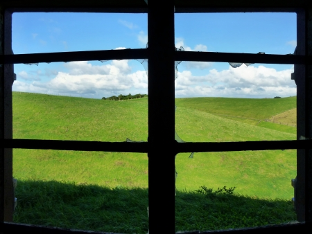 cielos azules: Ver a trav�s de la ventana rota de un puesto de defensa hist�rico en Motutapu Island, cerca de Auckland en prados verdes y cielos azules