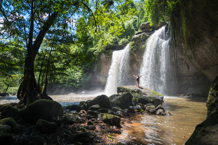 man waterfalls: Man looking at beautiful waterfalls in deep forest at Haew Suwat Waterfall in Khao Yai National Park, Thailand