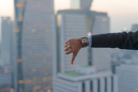 Thumbs down hand sign showing by businessman with cityscape  on modern building in Business district at Bangkok city background, Symbols concept Stock Photo