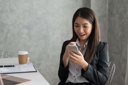 Excited asian business girl while reading a smart phone sitting in her workstation. Business Success Concept