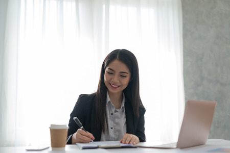 Businesswoman at work signing a contract paper in her workstation