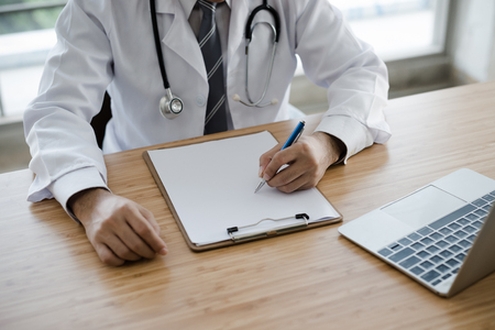 The doctors hands are writing at a desk.