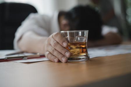 Beklemtoonde Aziatische zakenman die een glas whisky houdt hij en Gegevensgrafieken, bedrijfsdocument bij bureau slaapt. alcoholverslaving - dronken zakenman concept