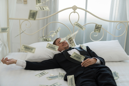 Young Businessman with happy, smile on the bed. who are successful in business and many banknote dollars money. business success concept Imagens