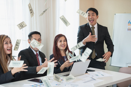 Asian business man and woman groups, successful business. There is a lot of money. with a laptop at office desk and document. business success concept