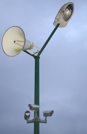 Isolated Green Pole with Grey Lamp, White Loudspeaker and Grey Security Cameras photo