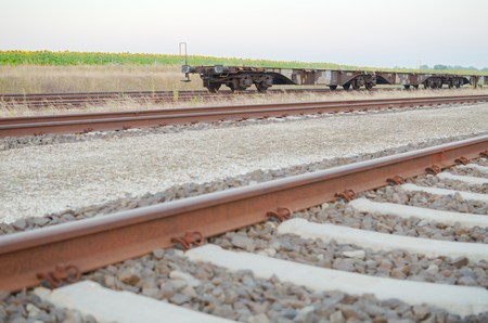 flatcar: Railway Tracks with Empty Open Wagons Sidewards in the Countryside Stock Photo