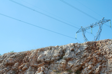 Electric Pylon over Cliff Face Protected by Wire Mash photo