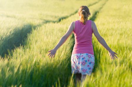 Woman Touching Green Unripe Barley Ears in Well Lit Field photo