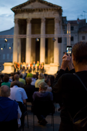 snapshot: Tourist Taking Snapshot with Smartphone of an Evening Cultural Program Vertical