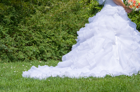 frilly: Traditional White Wedding Dress in the Green Summer Park Closeup
