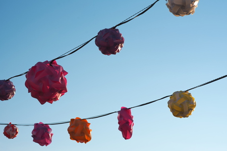 Backlit Twisted Plastic Lanterns Against Clear Blue Sky