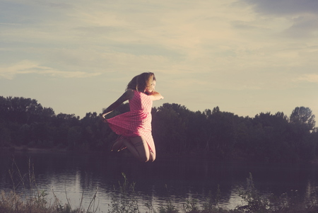Young Tattooed Woman Jumping over the Lake on a Summer Day