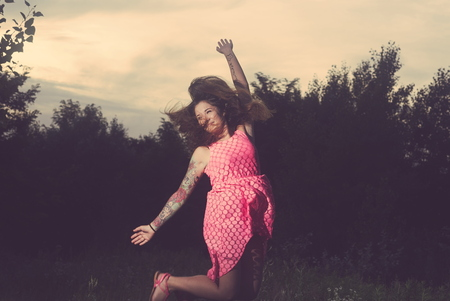 Young Tattooed Woman Jumping on a Forest Glade on a Summer Day