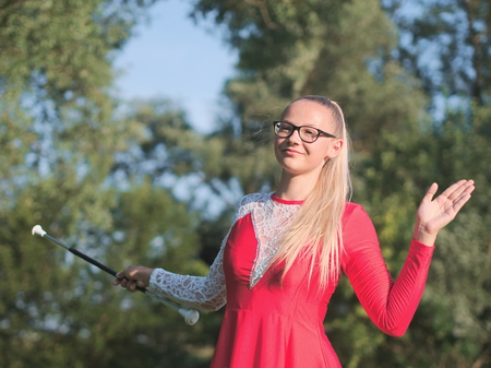 Bespectacled Blonde Teen Majorette Girl Twirling Baton Outdoors in Red Dress