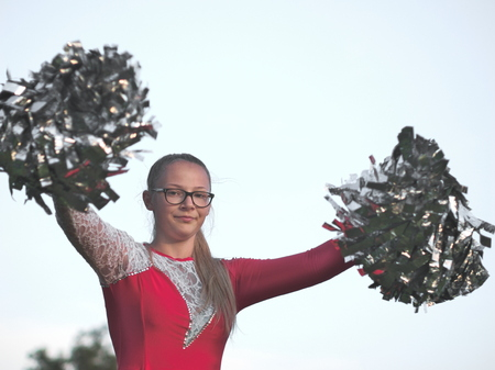 Bespectacled Blonde Teen Majorette Girl with Pom-poms Outdoors in Red Dress Foto de archivo