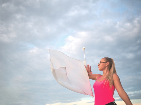 Bespectacled Blonde Teen Majorette Girl with White Flag Outdoors