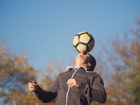Soccer Player Balancing Football in the Park on a Sunny Autumn Day