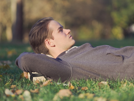 Soccer Player Lying in the Grass with Football in the Park on a Sunny Autumn Day Foto de archivo