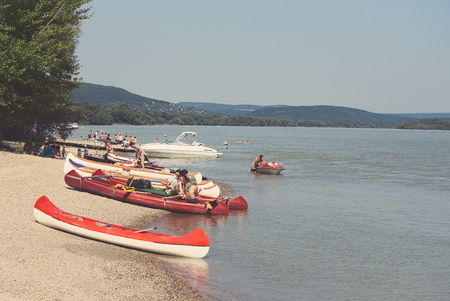 Vacation People on the Danube Beach with Red Canoe