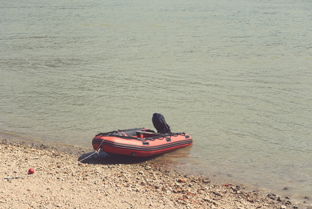 Red Rubber Motor Boat on the River Shore