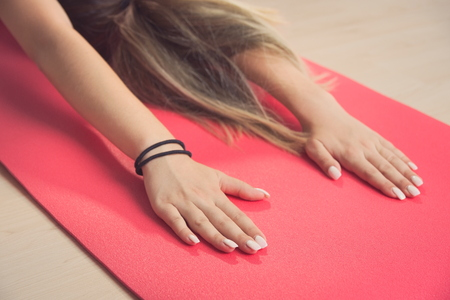 Teen Girl Stretching Arms on Red Yoga Mat Closeup Stock Photo