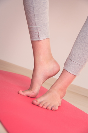 Teen Girl's Feet on Red Yoga Mat Closeup