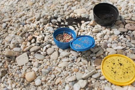 Maggots Fishing Bait in Blue Plastic Jar on Pebble Ground