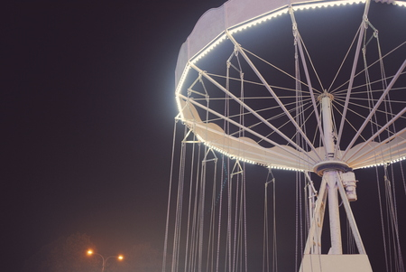 Floodlit White Chain Merry-go-round at Night Closeup