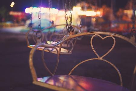 Chain Carousel Closeup with Town Fair Lights at Night