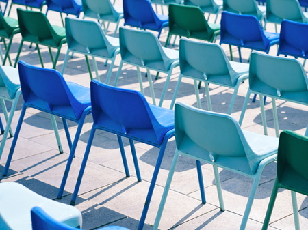 Many Empty Blue Plastic Chairs Outdoors on a Sunny Day