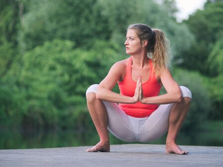 Woman in her Thirties Doing Yoga in the Park on a Pier Imagens