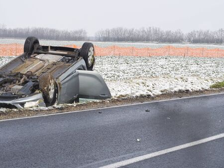 Overturned Car Beside the Wet Road on a Winter Day 版權商用圖片